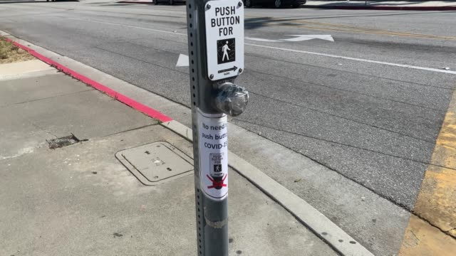 culver city public works street maintenance employees put tape on the walk buttons and signs around crosswalks encouraging pedestrians not to touch... - major road video stock e b–roll