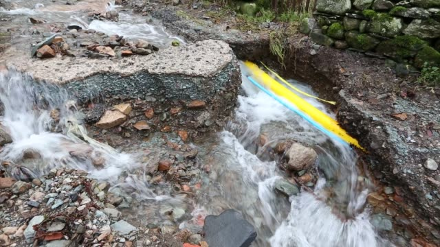 a culvert overflowing on blue hill, ambleside in the lake district on saturday 5th december 2015, during torrential rain from storm desmond. it has washed away a track revealing the gas pipe underneath. - rubble stock videos & royalty-free footage