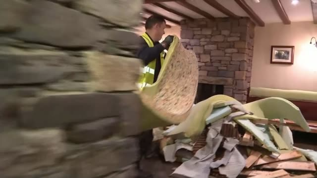 cumbria a year on from storm desmond december 2015 flood damaged furniture cleared from pub and man hoovering - カンブリア州点の映像素材/bロール