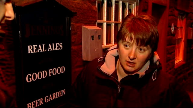 cumbria appleby grapes inn with sandbags at entrance helen hodgson inspecting flood defences with reporter floodgate across front door pull helen... - cumbria stock-videos und b-roll-filmmaterial