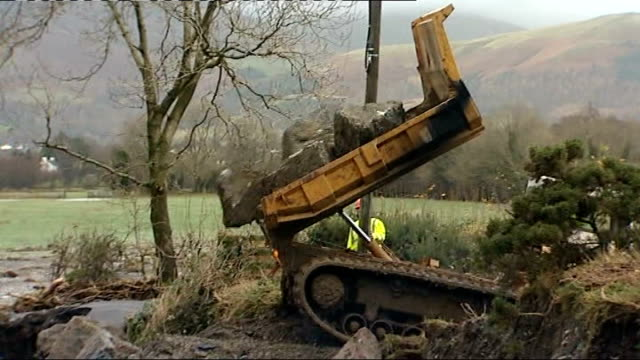 cockermouth ext mechanical digger moving rocks as carries out emergency repair work in river large rocks being dumped in river councillor jim... - in the loop 2009 film stock videos and b-roll footage
