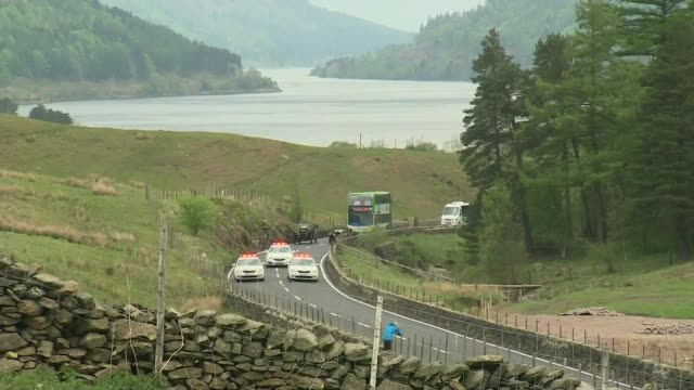 A591 road reopened EXT Parade of old cars and police cars along A591 ahead of reopening ceremony/ Rory Stewart MP cutting ribbon to reopen A591