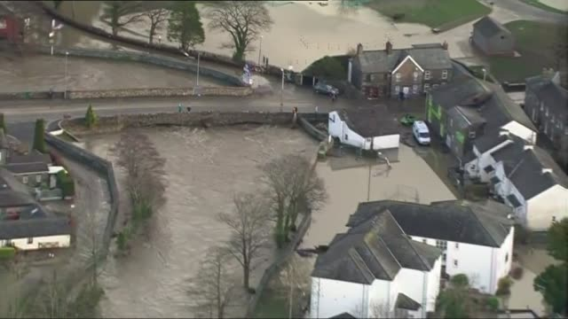 cumbria flooding aerials aerial views flooding in keswick / van along flooded road / zoom in flooded houses / flood water rushing along streets - cumbria stock-videos und b-roll-filmmaterial