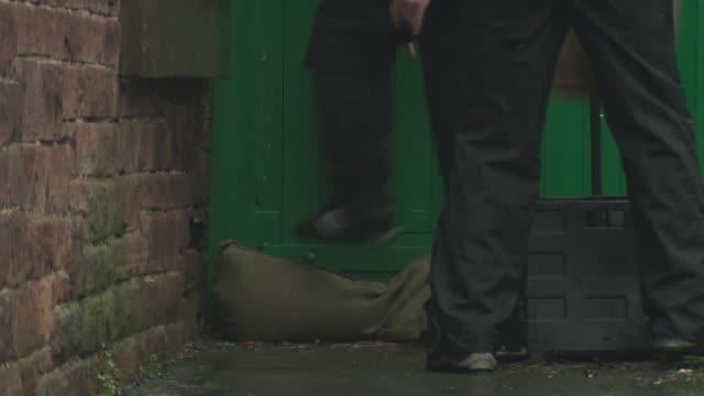 fears that floods will return england cumbria appleby ext **flood warning siren heard sot** people along street one carrying sandbags people standing... - cumbria stock-videos und b-roll-filmmaterial