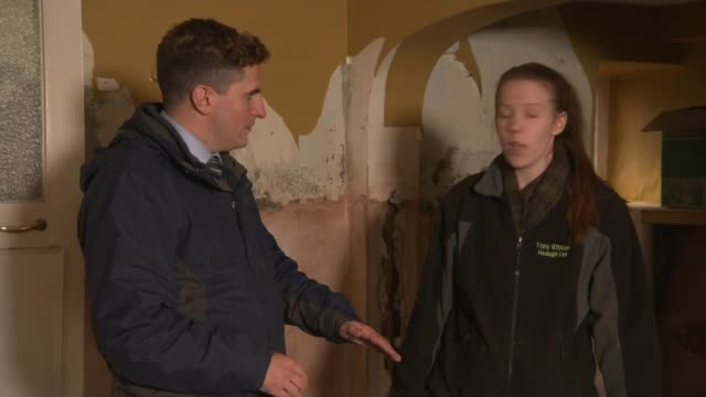 more weather warnings issued by met office charlotte ashley showing reporter around her flooddamaged home and interview sot - カンブリア州点の映像素材/bロール