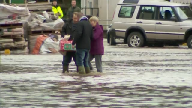 more weather warnings issued by met office england cumbria appleby ext woman along in ankle deep floodwater with shopping bags man sweeping water... - cumbria stock-videos und b-roll-filmmaterial