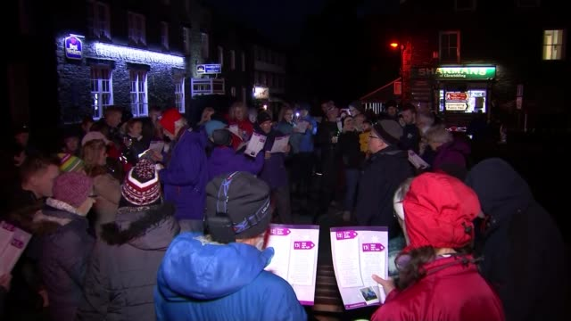 some areas flooded for third time in less than three weeks; glenridding: night **music heard sot** various shots of local residents singing christmas... - carol singer stock videos & royalty-free footage
