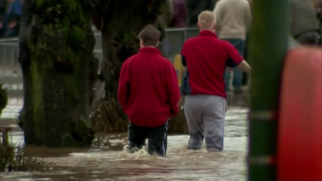 some areas flooded for third time in less than three weeks appleby flooded area partially submerged car back view two young men wading through... - カンブリア州点の映像素材/bロール