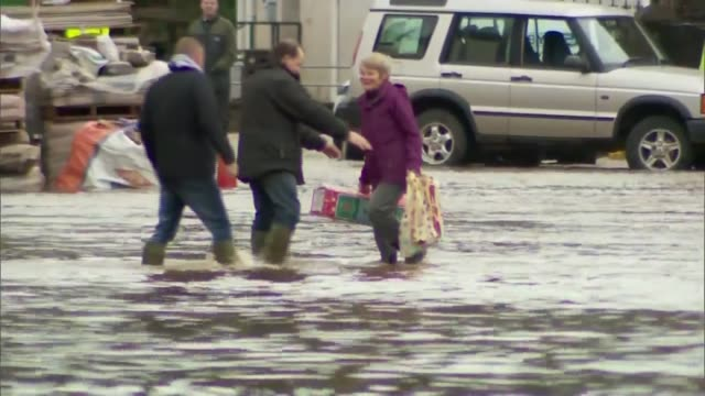 some areas flooded for third time in less than three weeks appleby woman wading through floodwater carrying bags back view two young men wading... - カンブリア州点の映像素材/bロール