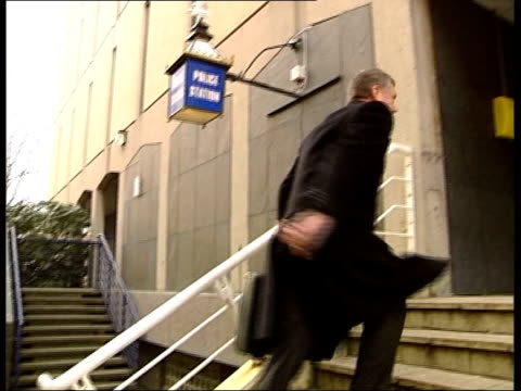 men questioned; itv evening news: tim rogers england: preston: ext solcitor along to police station pull out lamp outside police station solicitor... - itv evening news stock-videos und b-roll-filmmaterial