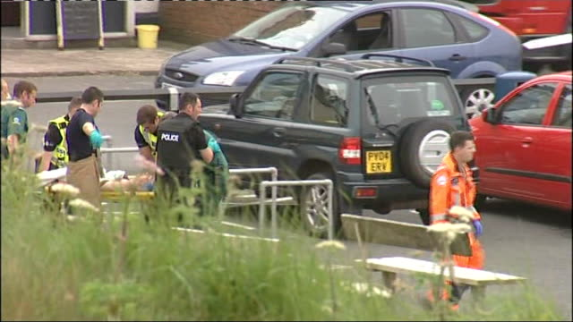 12 dead after gunman goes on rampage cumbria seascale ext person injured in shooting carried along on stretcher to helicopter - cumbria stock-videos und b-roll-filmmaterial