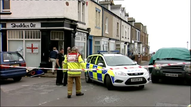 12 dead after gunman goes on rampage seascale police car along through cordon at crime scene - cumbria stock-videos und b-roll-filmmaterial