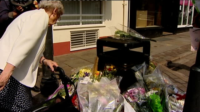 derrick bird was legal owner of guns england cumbria ext tribute flowers piled at scene of shooting local woman reading messages on flowers tribute... - derrick bird cumbria stock-videos und b-roll-filmmaterial