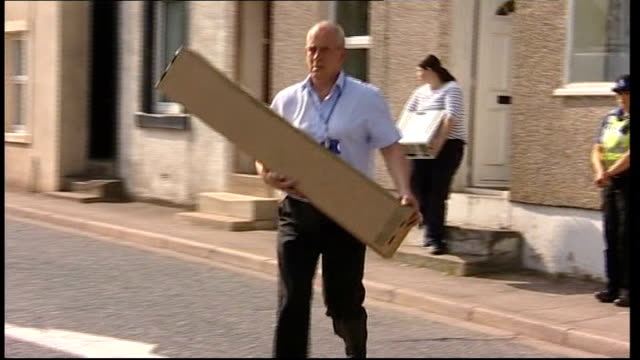 derrick bird was legal owner of guns england cumbria rowrah ext police officer and woman carrying packages out of derrick bird's home police officer... - derrick bird cumbria stock-videos und b-roll-filmmaterial
