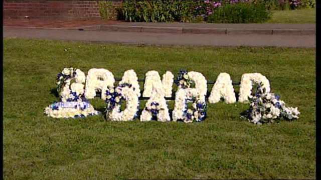funerals of victim and derrick bird take place cumbria people along to building for funeral of gunman derrick bird and wreaths spelling out 'grandad'... - derrick bird cumbria stock-videos und b-roll-filmmaterial