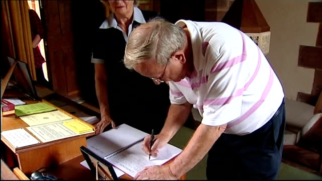 home video of derrick bird on holiday shown by media england cumbria whitehaven int man signing condolence book inside church burning candle pull rev... - derrick bird cumbria stock-videos und b-roll-filmmaterial