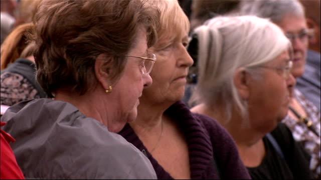 memorial services held across west cumbria england cumbria ext women standing at memorial service as bell tolls sot - cumbria stock-videos und b-roll-filmmaterial