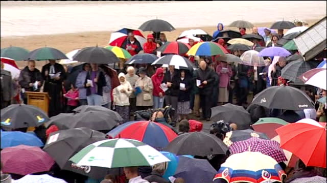 stockvideo's en b-roll-footage met remembrance services held for victims; england: cumbria: seascale: ext / raining high shot of people standing under umbrellas as singing 'the lord is... - itv weekend evening news