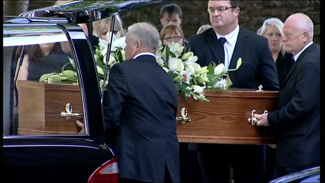 susan hughes and kenneth fishburn funerals held england cumbria egremont ext pallbearers removing coffin of susan hughes from hearse - カンブリア州点の映像素材/bロール