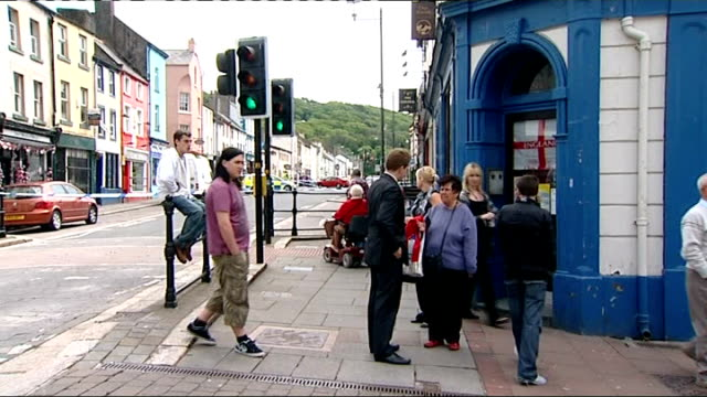 whitehaven shooting aftermath onlookers standing outside high street pub/ police cars and police officers in cordoned off high street - cumbria stock-videos und b-roll-filmmaterial