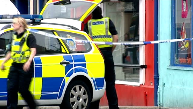 whitehaven shooting aftermath police cars and police officers in cordoned off high street - cumbria stock-videos und b-roll-filmmaterial