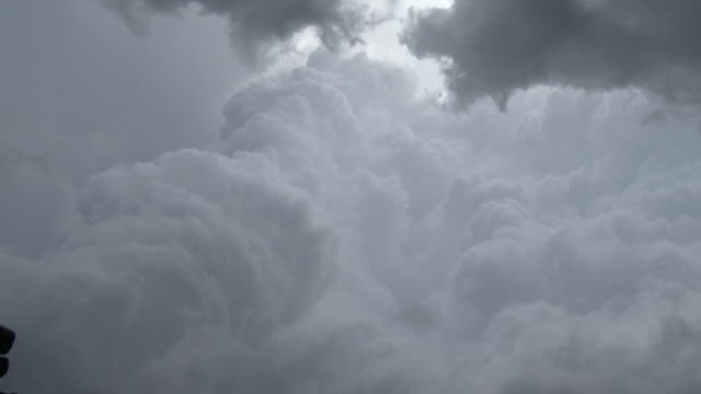 vídeos de stock, filmes e b-roll de cumulonimbus clouds associated with a rotating supercell thunderstorms updraft rise high into the sky and take on a corkscrew appearance - sacarrolha