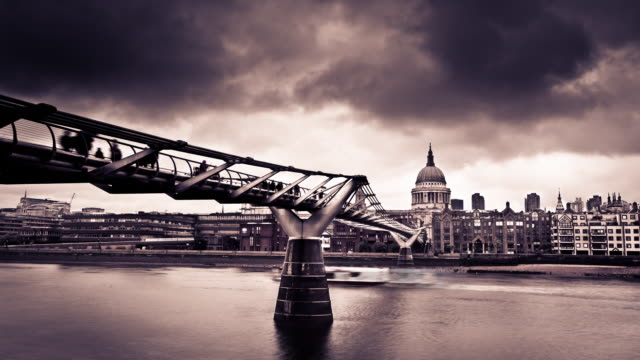 Cumulonimbus clouds race above Millennium Bridge and St. Paul's Cathedral in a time lapse of London.