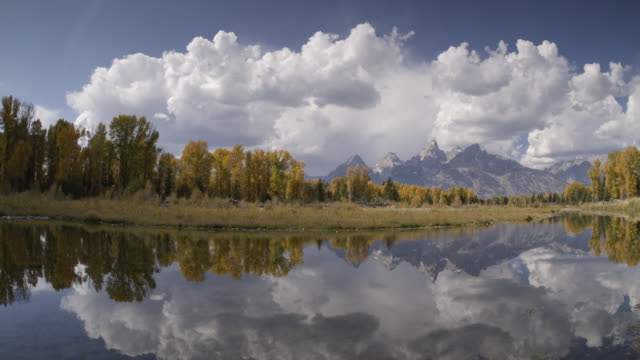 T/L WS Cumulous clouds moving above yellow-leafed cottonwood trees reflected in Snake River, Teton Mountains in distance, Grand Teton National Park, Wyoming, USA