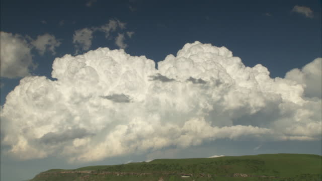 Cumulus clouds billow over a green hill in a time lapse of South Africa. Available in HD