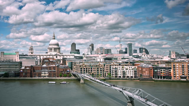 cumulus clouds drift above the thames river near millennium bridge and st. paul's cathedral in a time lapse of london. - london millennium footbridge stock videos & royalty-free footage