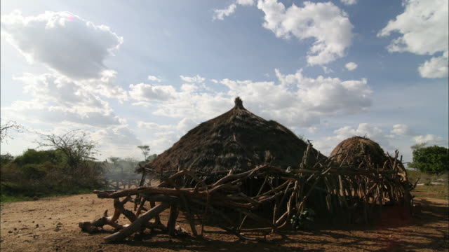 cumulus clouds drift over a grass hut in benin. - grass hut stock videos & royalty-free footage