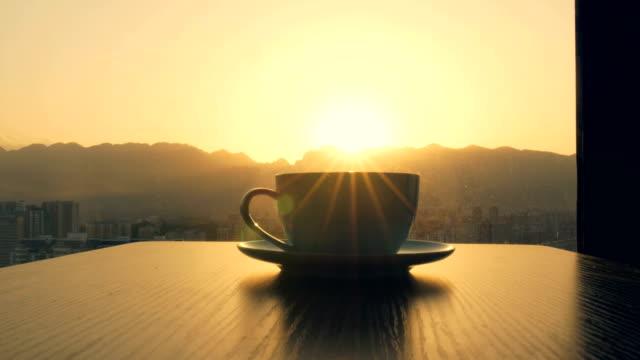 tasse kaffee auf holztisch für fenster - kaffeetasse stock-videos und b-roll-filmmaterial