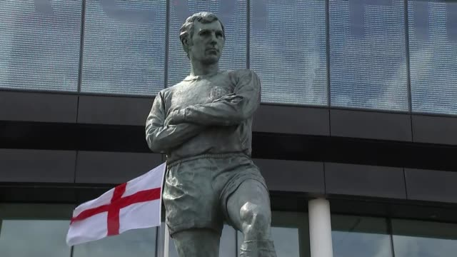 Arsenal and Aston Villa fans at Wembley ENGLAND London Wembley Stadium EXT Worker cleaning the statue of England World Cup winning Captain Bobby...