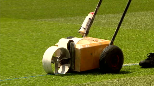 arsenal beat hull city groundsman pushing line painting machine along pitch - itv weekend evening news点の映像素材/bロール