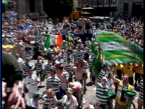 celtic v porto itn spain seville cms piper playing bagpipes pan glasgow celtic fans waving flags in town square before uefa cup final against porto... - tartan stock videos & royalty-free footage