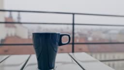 CU Cup of a hot drink on a table on a balcony in the city