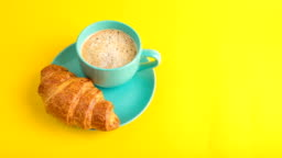 A cup of cappuccino coffee and a croissant. Bright yellow background. eating breakfast. bite off dessert baking. Video footage stop motion timelapse. Coffee take away ( to go )