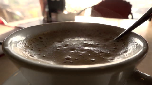 Cup of capuccino stirring with spoon
