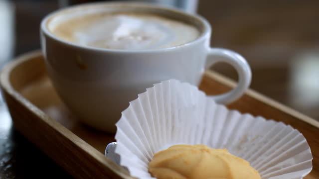 vídeos de stock e filmes b-roll de cup of coffee and cookie in coffee shop - atividades de fim de semana