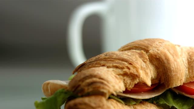 vídeos de stock, filmes e b-roll de hd: xícara de café e sanduíche de croissant - crocante