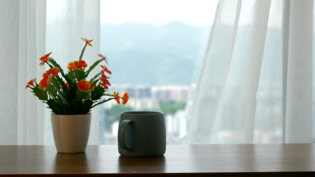 vídeos de stock e filmes b-roll de cup of coffee and flower on the table by the curtain - curtain