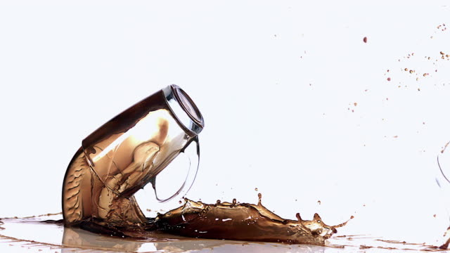MS SLO MO Cup of coffee falling, spilling and splashing on floor against white background / Vieux Pont, Normandy, France