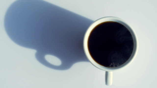 dolly shot: cup of coffee from above with natural steam - white background stock videos & royalty-free footage