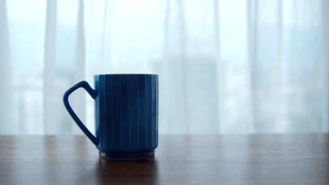 vidéos et rushes de cuvette de café sur la table par la fenêtre - vapeur