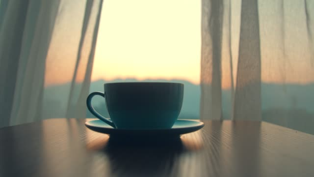 cup of coffee on table with blowing curtain - coffee break stock videos & royalty-free footage