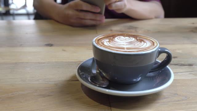 vídeos de stock, filmes e b-roll de xícara de café na mesa de madeira com homem usando telefone inteligente fundo na cafeteria. - madeira