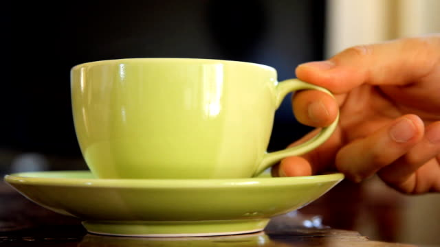 cup of coffee, tea, or hot drink beverage with steam, with hand picking up and put down