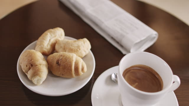 Cup of coffee with croissant and newspaper