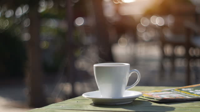 a cup of fresh hot drink on table with real steam on it, outdoors in autumn - coffee table stock videos & royalty-free footage