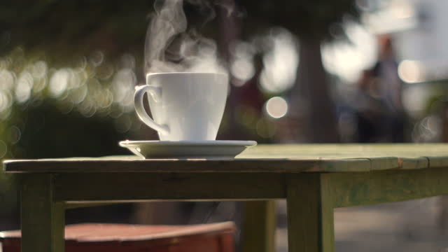 a cup of fresh hot drink on table with real steam on it, outdoors in autumn - saucer stock videos & royalty-free footage